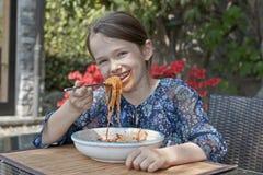 A menina está comendo o espaguete Imagem de Stock Royalty Free