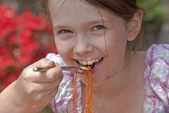 A menina está comendo o espaguete Imagens de Stock Royalty Free