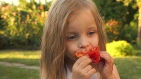A menina está comendo um tomate video estoque