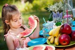 A menina está comendo uma melancia em um piquenique no parque Fotografia de Stock Royalty Free