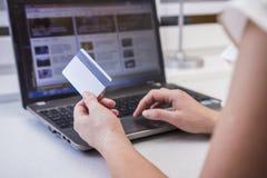 A menina está comprando no Internet Nas mãos de um cartão de crédito plástico Uma mulher na frente de um monitor do computador na fotos de stock