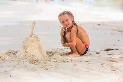 A menina está construindo nos castelos de areia da praia no dia ensolarado do verão Foto de Stock