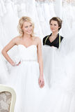 A menina está contente de pôr sobre este vestido de casamento imagens de stock