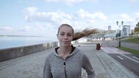 A menina está correndo atrás da câmera Movimento da manhã ao longo da terraplenagem do Rio Volga vídeos de arquivo
