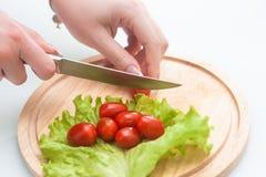 A menina está cortando tomates de cereja Imagem de Stock Royalty Free