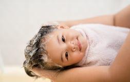 A menina está dando-lhe uma lavagem hiar Fotos de Stock Royalty Free