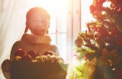A menina está decorando a árvore de Natal fotografia de stock