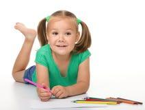 A menina está desenhando ao colocar no assoalho fotografia de stock royalty free