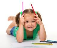 A menina está desenhando ao colocar no assoalho foto de stock