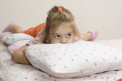 A menina que encontra-se e que esconde sua cara no descanso que olha direito Foto de Stock