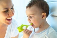 A menina está escovando os dentes com sua escova de dentes imagem de stock royalty free