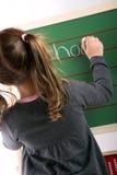 A menina está escrevendo em uma placa Fotos de Stock Royalty Free