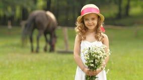 A menina está estando em um parque com um ramalhete dos wildflowers Movimento lento video estoque