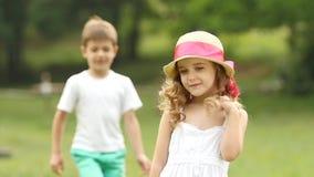 A menina está estando no parque, atrás dela é um rapaz pequeno Movimento lento video estoque