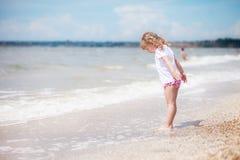 A menina está estando pelo mar Imagem de Stock Royalty Free
