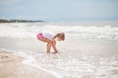 A menina está estando pelo mar foto de stock