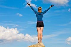 A menina está estando sobre a rocha e aprecia o sol Fotos de Stock Royalty Free