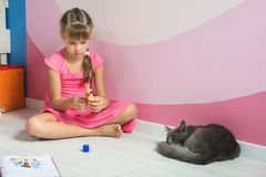 A menina está fazendo figuras fora do papel colorido, um gato doméstico está dormindo próximo fotos de stock