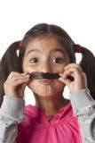 A menina está fazendo um moustache de seu cabelo Fotografia de Stock Royalty Free