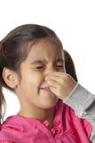 A menina está fechando seu nariz com seus dedos Fotografia de Stock