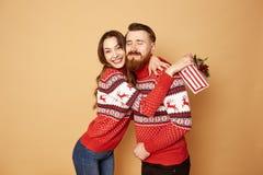 A menina está feliz com o indivíduo que dá a que um presente do Natal é vestido em camisetas vermelhas e brancas com cervos e imagens de stock