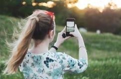 A menina está fotografando o por do sol no telefone para trás vê fotos de stock