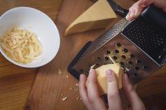 A menina está friccionando o queijo holandês Foto de Stock Royalty Free