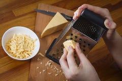 A menina está friccionando o queijo holandês Imagens de Stock Royalty Free