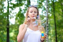 A menina está fundindo bolhas Imagem de Stock