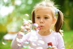 A menina está fundindo bolhas de sabão Imagem de Stock Royalty Free
