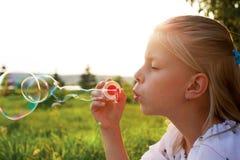 A menina está fundindo bolhas de sabão imagens de stock royalty free