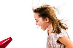A menina est? gritando, gritaria no secador do sopro - secador de cabelo fotografia de stock royalty free