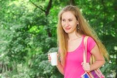 A menina está guardando a bebida no parque Imagem de Stock Royalty Free