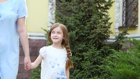 A menina está guardando a mão da sua mãe e está andando ao longo da rua vídeos de arquivo