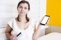 A menina está guardando o cartão do pagamento do smartphone e do plástico em sua mão Compras em linha no telefone imagem de stock