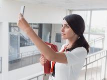 A menina está guardando o telefone em suas mãos A mulher de negócios de sorriso bonita está chamando pelo telefone Retrato da mul Fotografia de Stock