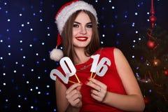 A menina está guardando os dígitos de papel 2016, tempo do Natal Foto de Stock Royalty Free