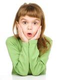A menina está guardando sua cara na admiração imagens de stock