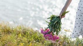 A menina está guardando um ramalhete de peônias cor-de-rosa de florescência bonitas Suas vibrações brancas do vestido no vento foto de stock