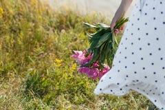 A menina está guardando um ramalhete de peônias cor-de-rosa de florescência bonitas Suas vibrações brancas do vestido no vento Id fotos de stock royalty free