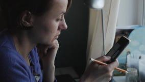 A menina está guardando um smartphone e está lançando-o através das imagens vídeos de arquivo