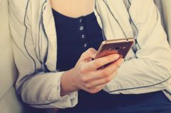 A menina está guardando um telefone celular Close-up imagem de stock royalty free