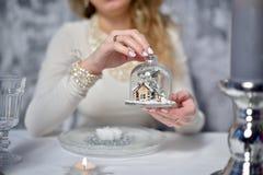 A menina está guardando uma casa pequena sob o bulbo de vidro em sua mão Fotos de Stock Royalty Free