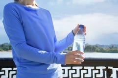 a menina está guardando uma garrafa da água fotos de stock royalty free