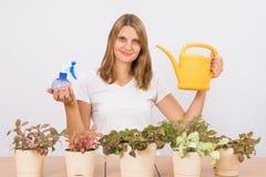 A menina está guardando uma garrafa do pulverizador e uma lata molhando para importar-se com flores foto de stock