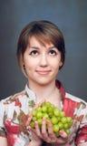 A menina está guardarando a uva verde Fotografia de Stock