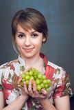 A menina está guardarando uvas frescas Fotos de Stock