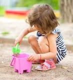 A menina está jogando com a areia no campo de jogos Imagem de Stock