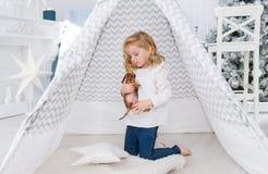 A menina está jogando com o cão de cachorrinho pequeno perto da tenda na sala de jogos do Natal foto de stock