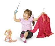 A menina está jogando com tesouras Fotografia de Stock